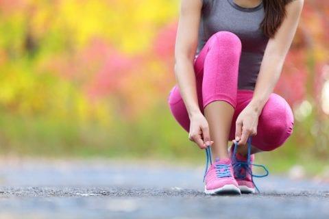 Runningshoes womantyingshoelacescloseupof