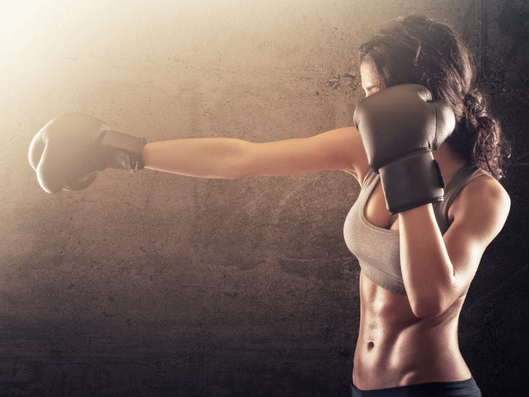Strong athletic woman with gloves punching