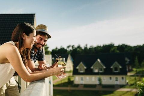 Fröhliche Menschen mit Weingläsern auf dem Balkon